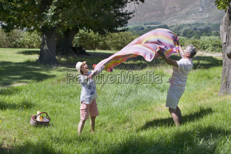 senior couple lying picnic blanket in