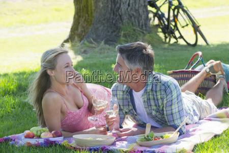 couple drinking wine lying on picnic