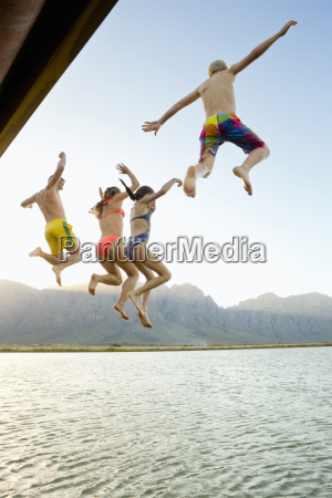 family in swimwear jumping into a