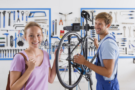 cycle technician repairing female customers bicycle