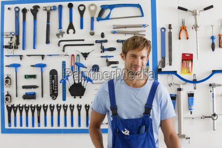cycle technician in workshop looking at
