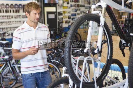 man choosing a bicycle in shop