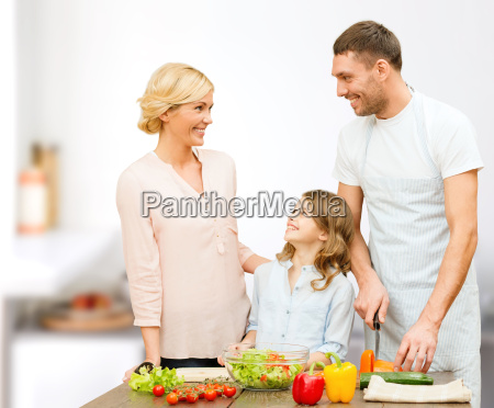 happy family cooking vegetable salad for
