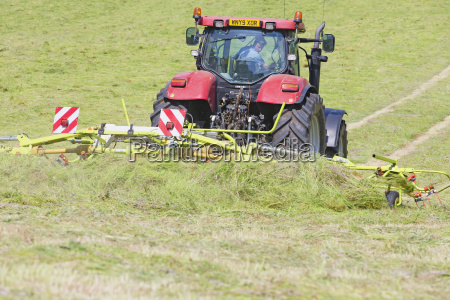tractor turning cut grass to dry