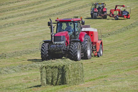 tractors and bale wrapper baling hay