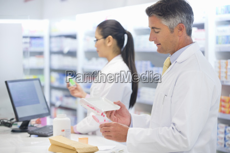 pharmacist counting and dispensing medication behind