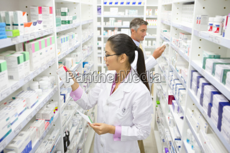 pharmacist holding prescription looking at medication