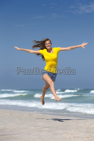happy woman with arms outstretched leaping