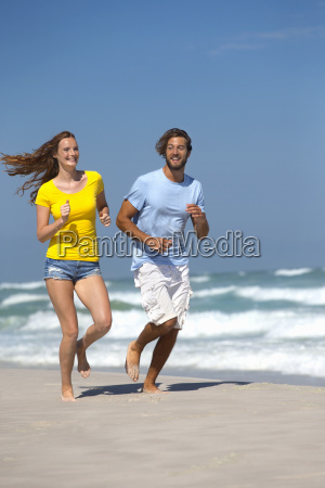 happy couple smiling and running on