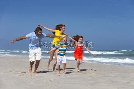 happy family pretending to fly running