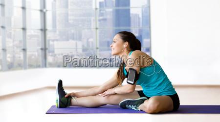 smiling woman stretching leg on mat