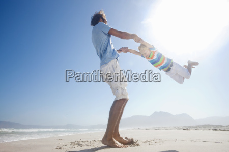 father swinging son in the air