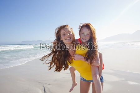 smiling mother giving daughter piggy back