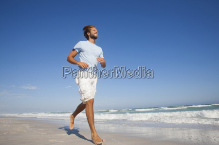 smiling man running on sunny beach