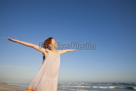 happy girl with arms raised to