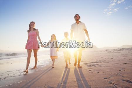 happy family walking toward camera holding