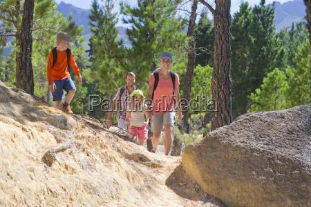 family hiking on mountain path