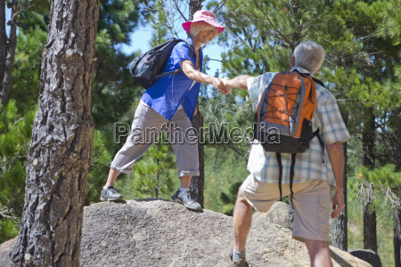 senior couple helping each other hiking