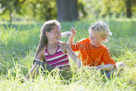 young boy tickling young girl with