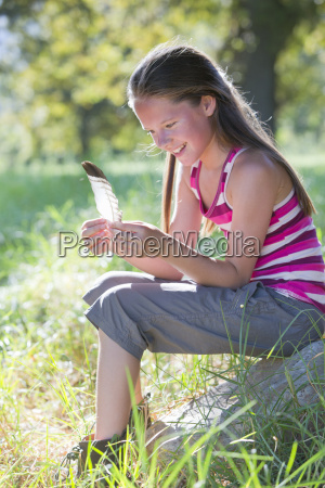 smiling girl looking at feather sitting