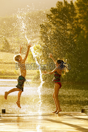 young boy and girl jumping in