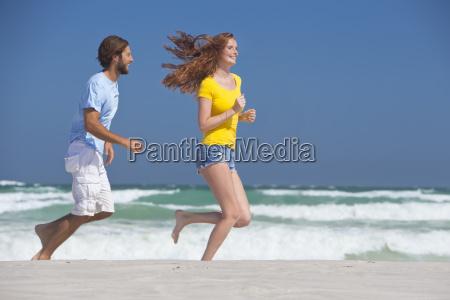 happy couple running on sunny beach