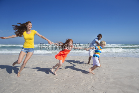 happy family holding hands running and