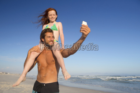 father with daughter sitting on shoulders