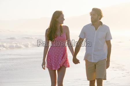 couple holding hands walking along sunny