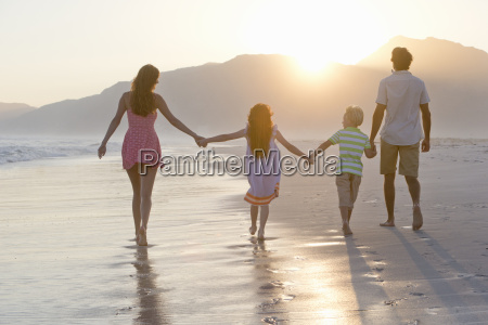 happy family walking into distance holding