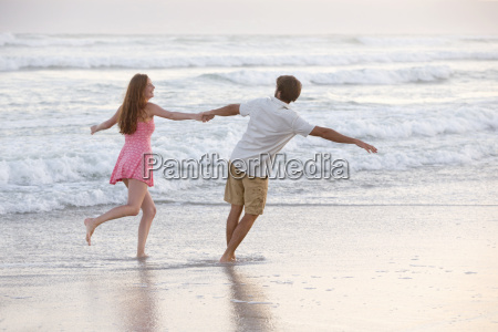 couple holding hands playfully running through