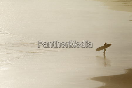 surfer carrying surf board walking along