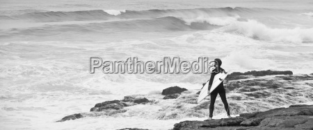 man with surfboard standing on rocks