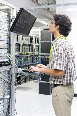 technician working on computer in server