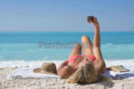 woman taking selfie lying on towel