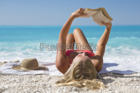 woman reading book lying on towel