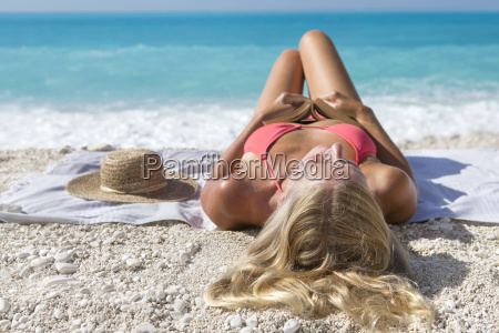 woman holding book lying on towel