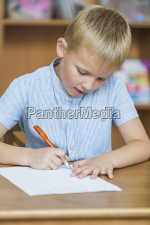 close up of boy writing on