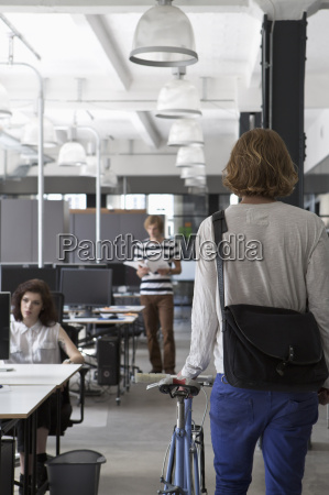 man entering in office with bicycle