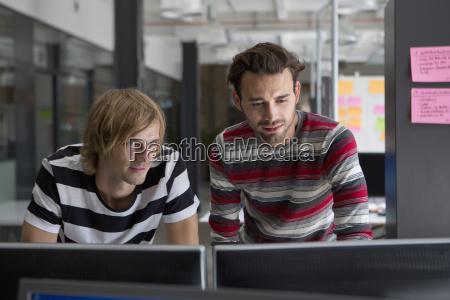 two men working on computer in