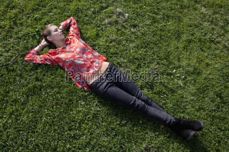 young woman lying on grass in