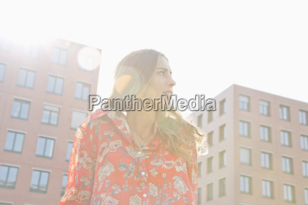 young woman standing under sunshine buildings