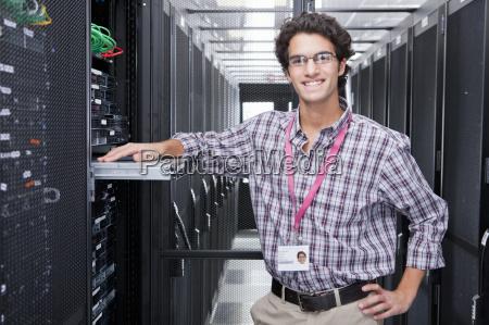 technician smiling at camera replacing server