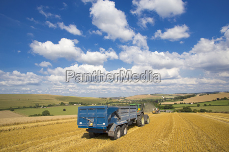 tractor pulling trailer with straw bales