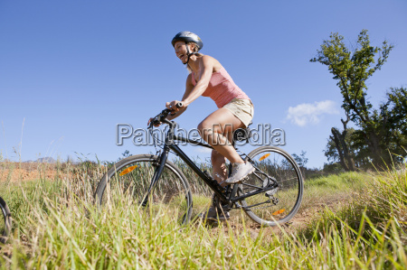 woman mountain biking on country track