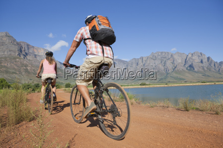 couple mountain biking in countryside by