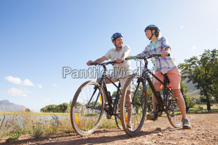 senior couple mountain biking on country