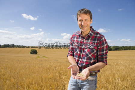 portrait smiling farmer examining sunny rural