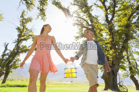 couple walking with picnic bottles in