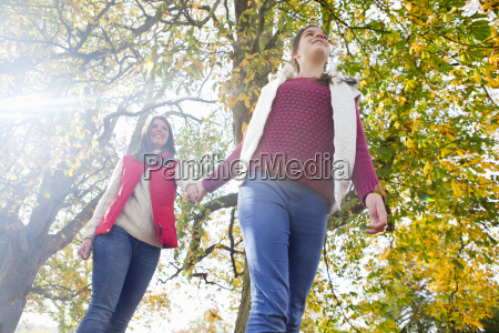 mother and daughter walking through autumnal